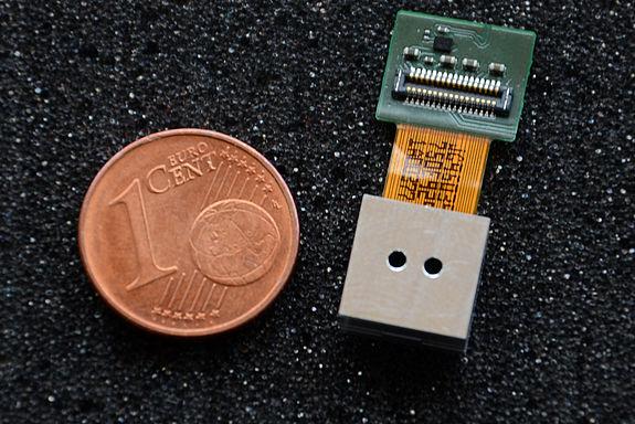 Bild einer Multiaperturkamera mit 3mm Baulänge im Vergleich mit einer 1Cent Münze