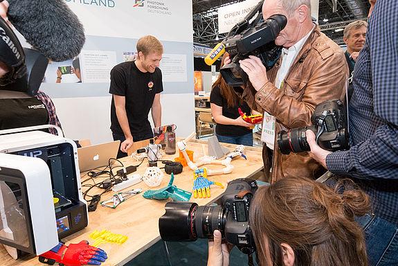 Journalisten drängen sich um einen Tisch mit 3D-Druckern und bunten Plastikteilen