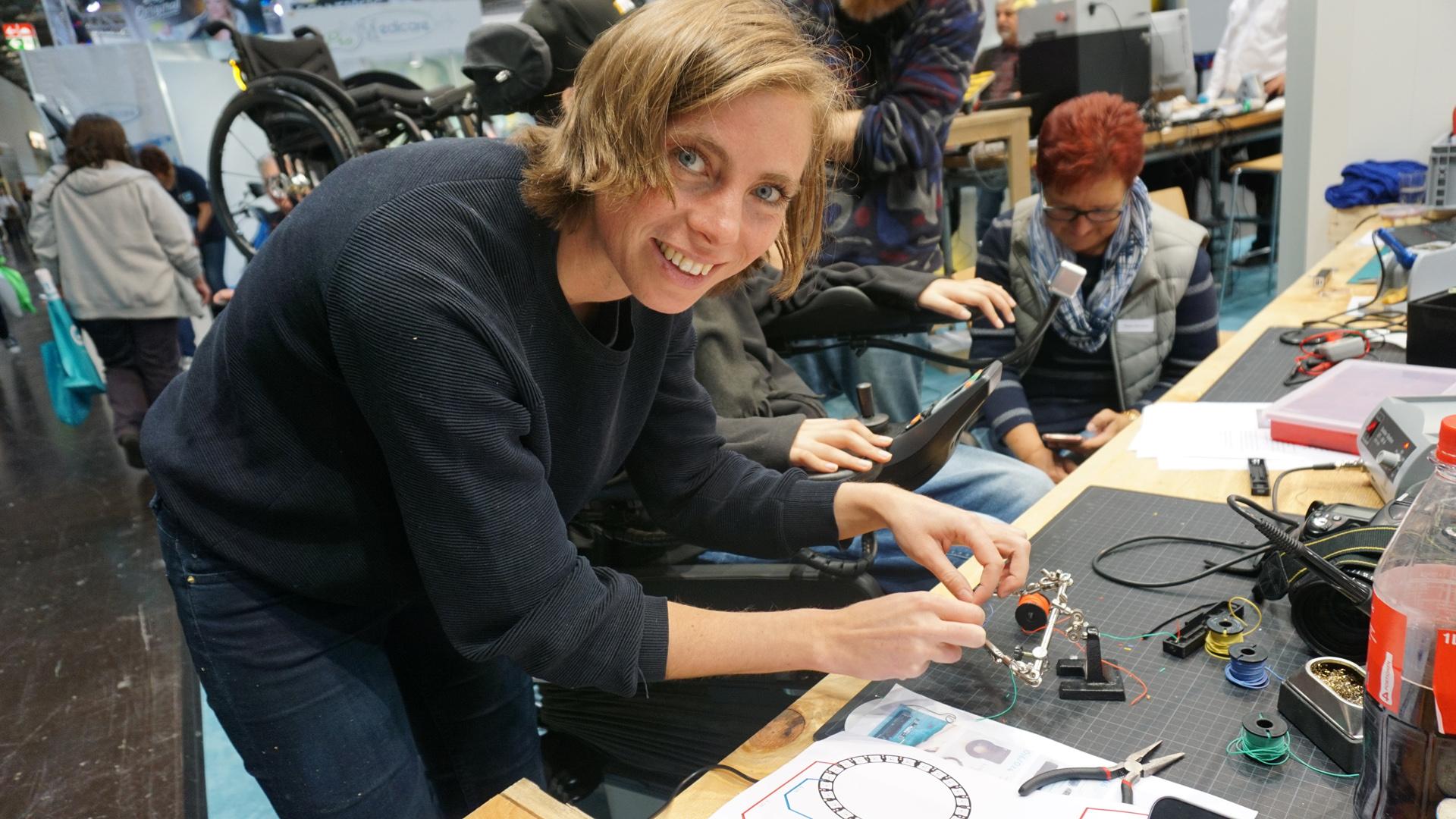 Eine Frau schaut lächelnd in die Kamera, während sie kleine Drähte zum Löten in der Hand hält.