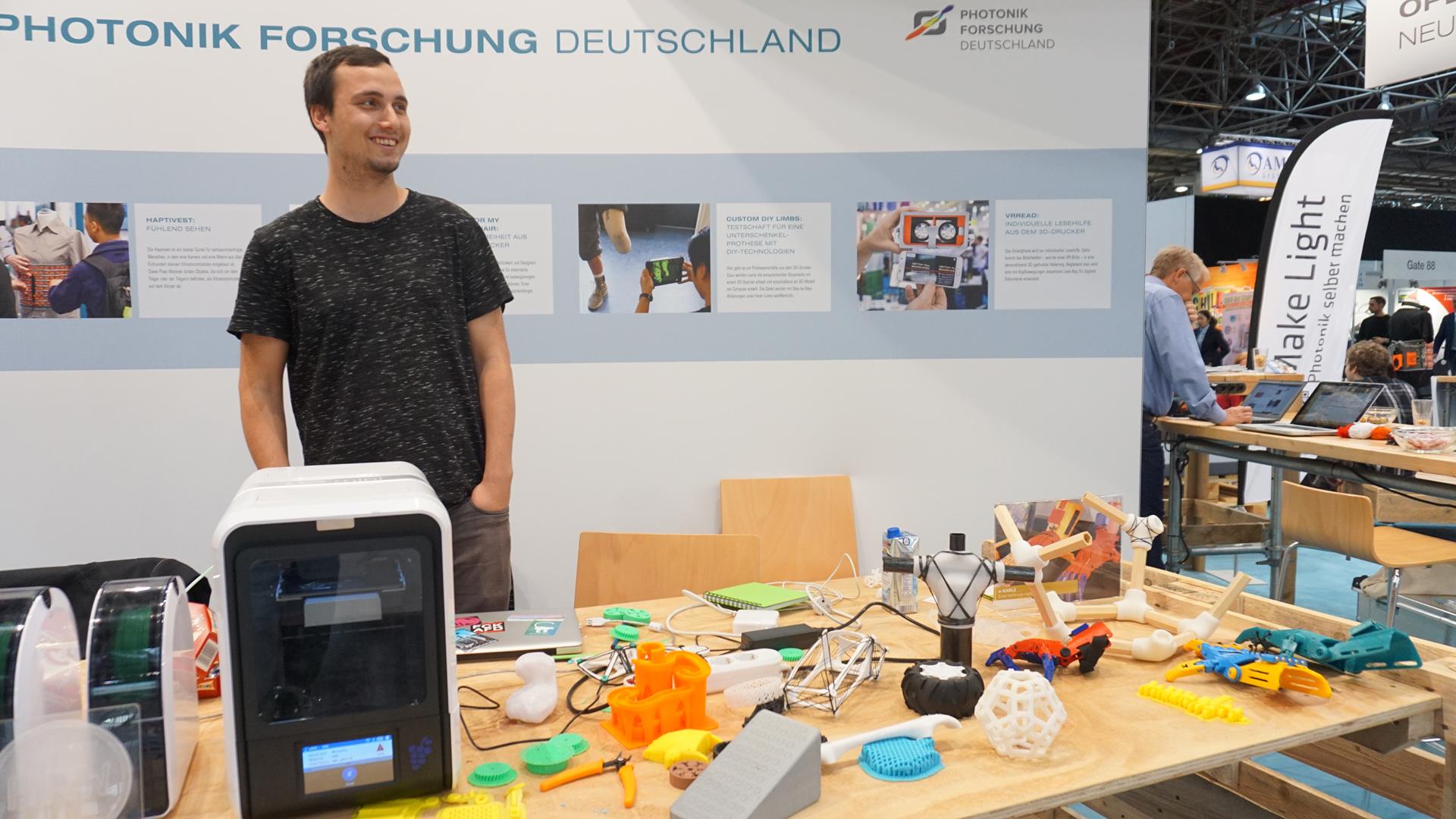 Auf einem Messetisch steht ein 3D-Drucker mit einigen bunten 3D-gedruckten Teilen, dahinter steht ein Mann.