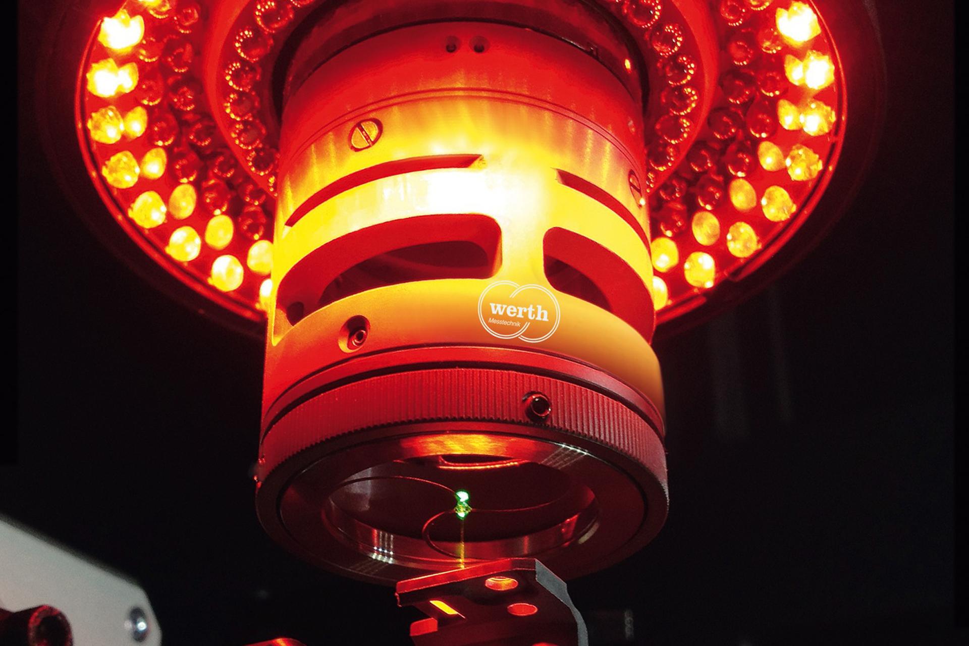 Ein runder Sensormesskopf mit rötlich leuchtenden Lampen.
