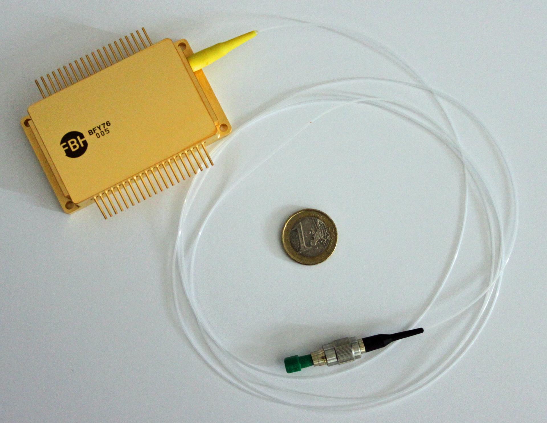 Kleine kompakte und rechteckige Box mit einer langen Faser, an deren Ende ein kleiner Laserkopf befestigt ist.