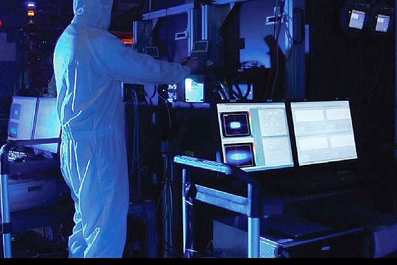 Arbeiter im Schutzanzug an Laser-System