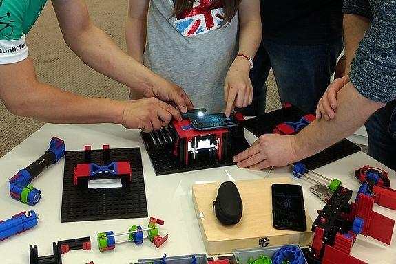 Teile des Baukastens auf einem Tisch, junge Besucher bauen ein photonisches System auf.