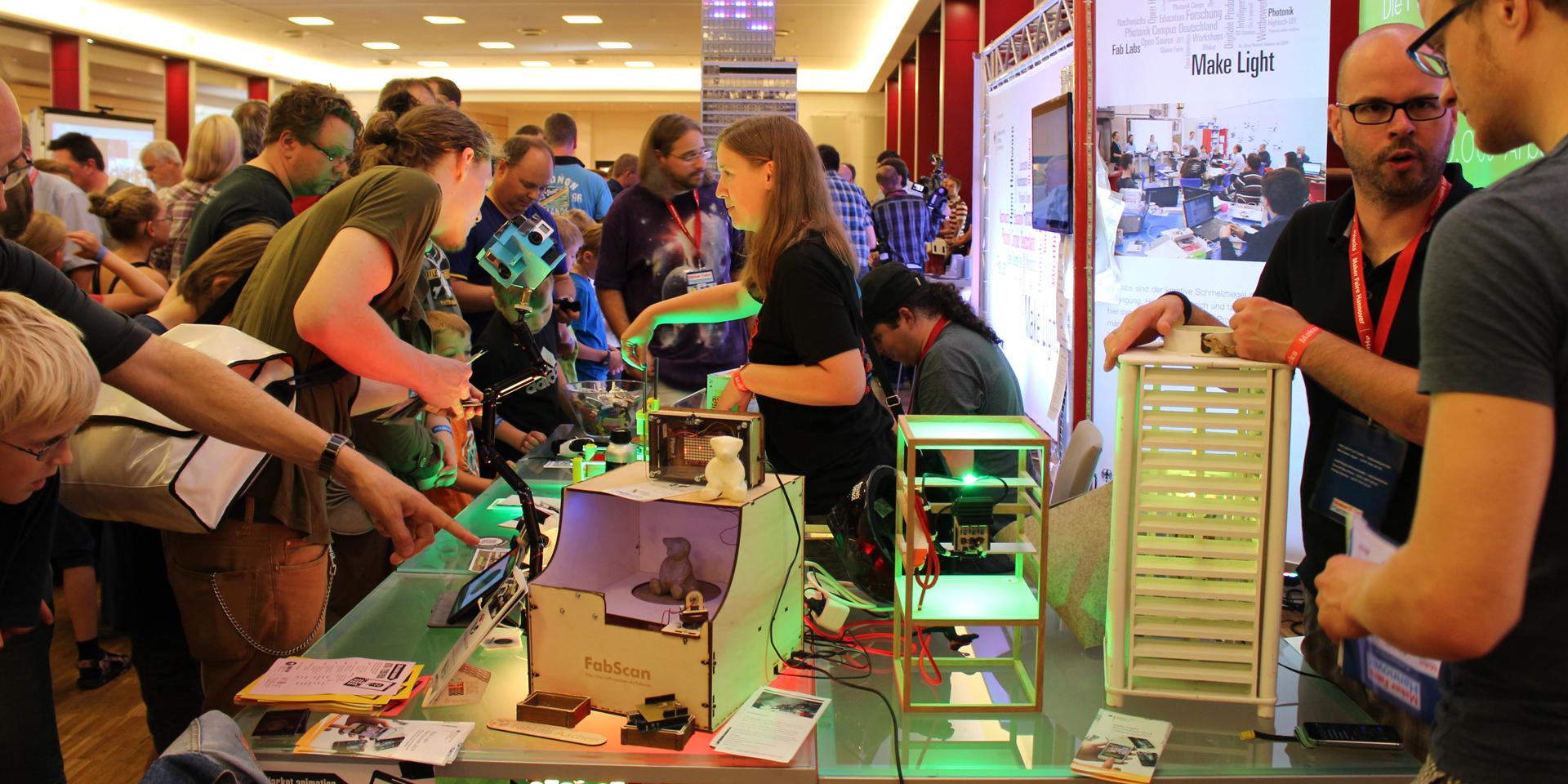 Menschen drängen sich um einen Tisch mit vielen leuchtenden elektronischen Dingen