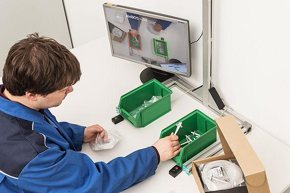 Mann sortiert Kleinteile in zwei Kästen, ein Bildschirm zeigt dabei sofort an, welcher der richtige Kasten ist
