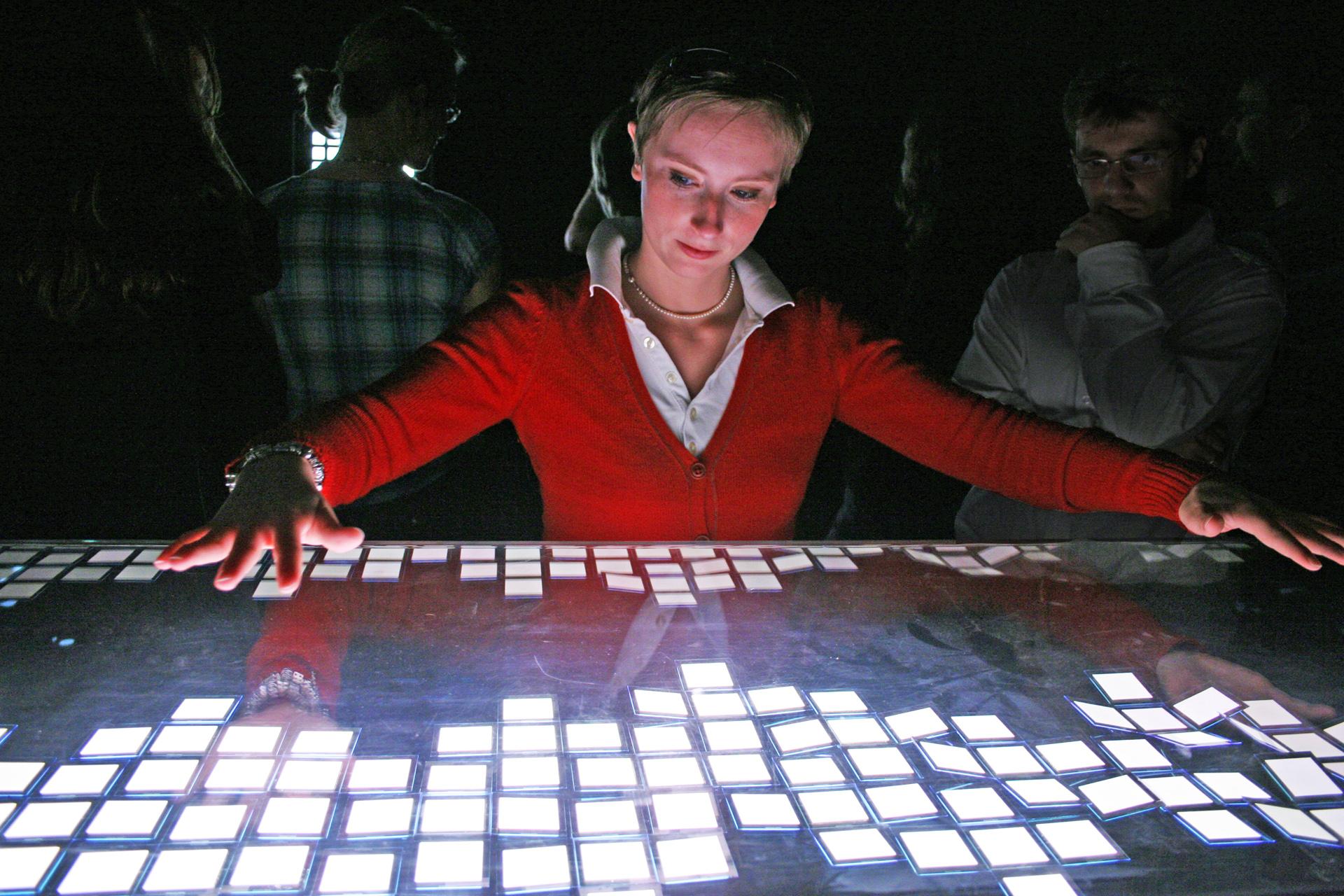 Eine Studentin hat fasziniert die Arme über hell leuchtende, rechteckige OLED-Kacheln ausgebreitet.