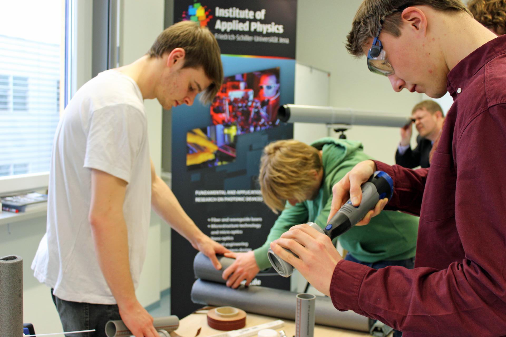 Drei Studierende bauen mit Plastikrohren aus dem Baumarkt ein Teleskop