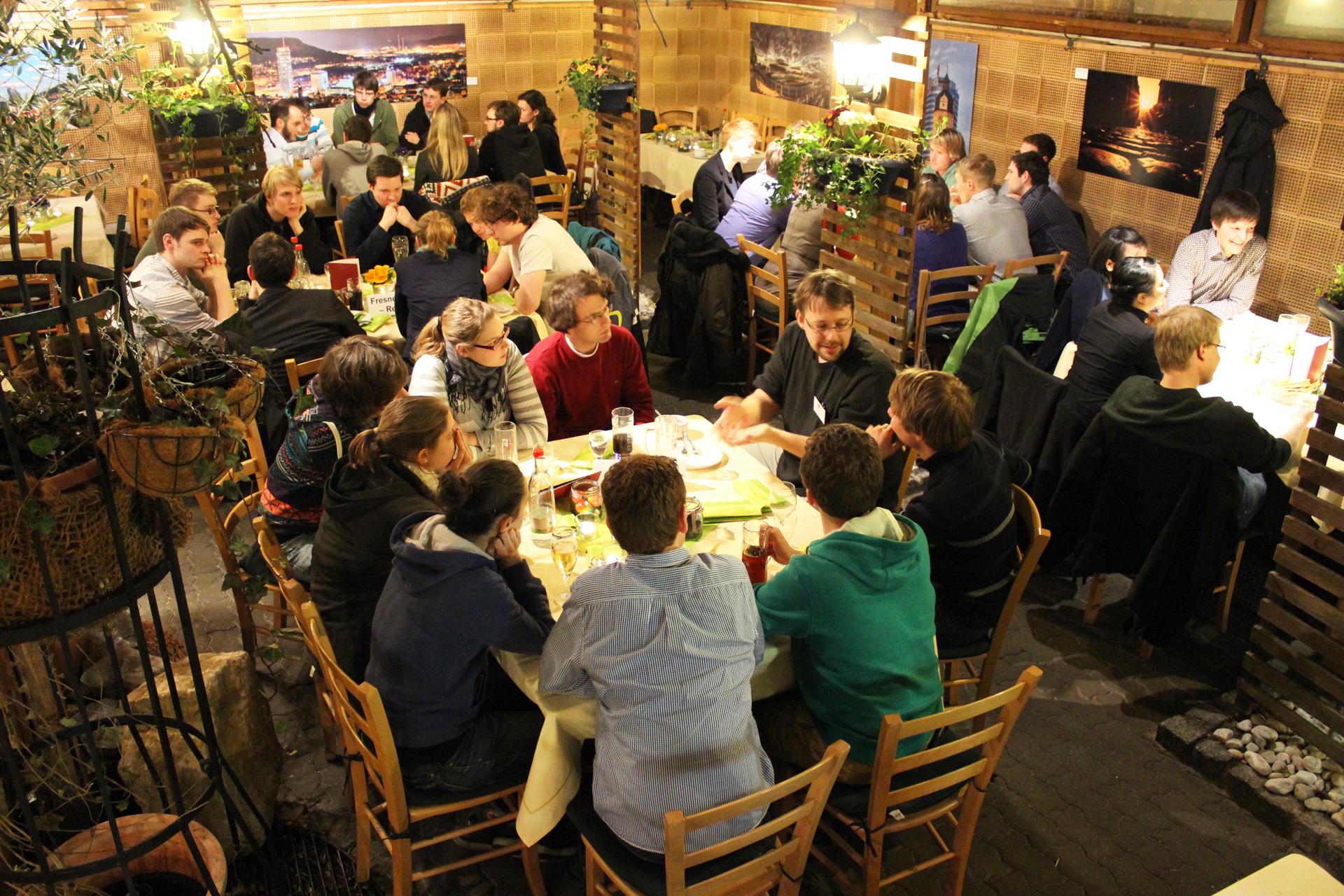 Blick über einen gemütlichen Raum mit mehreren Tischen, an denen instesamt rund 30 Menschen sitzen