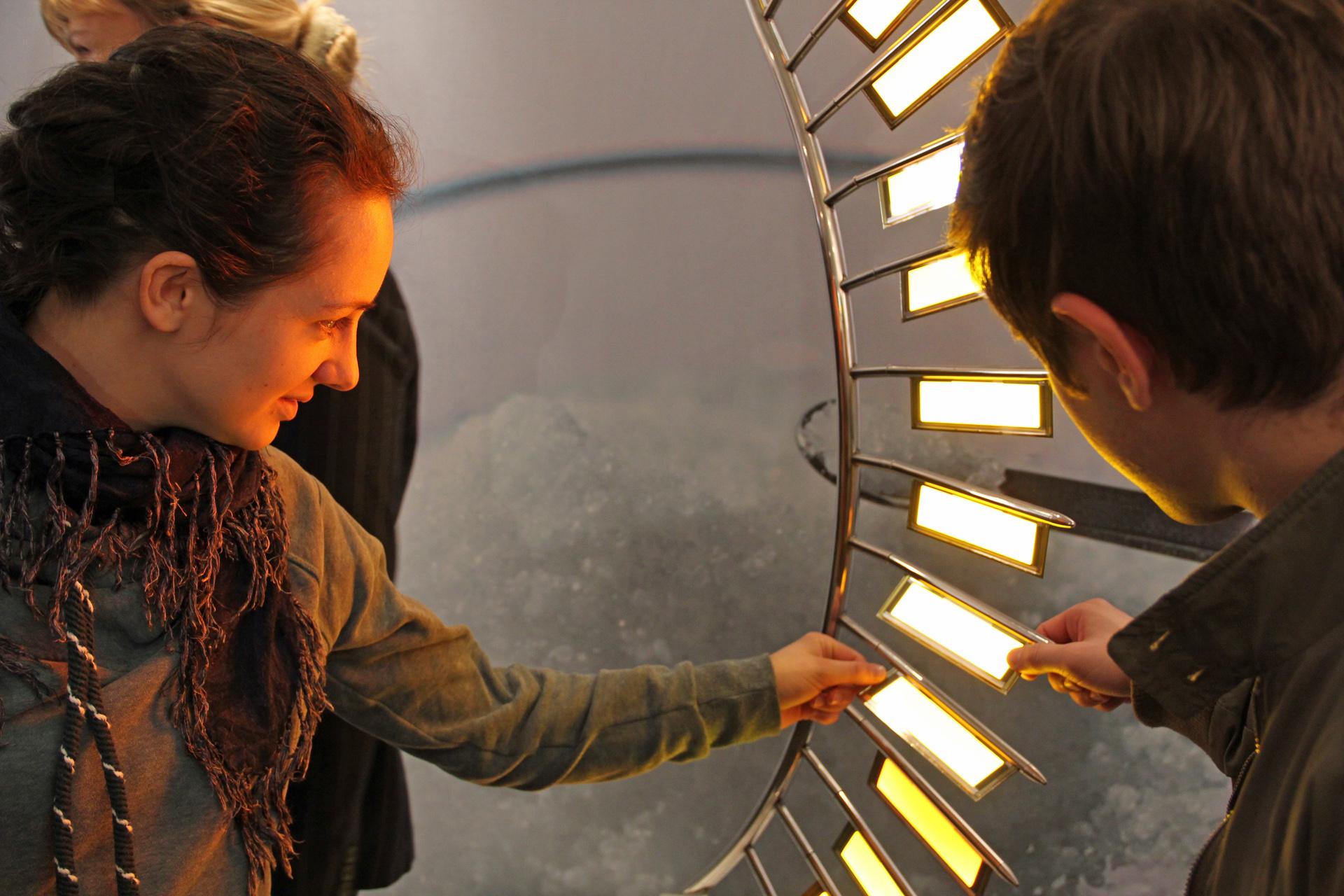 Eine Studentin fasst fasziniert eine OLED-Lampe an, die wie ein risiger Farn desingt ist.