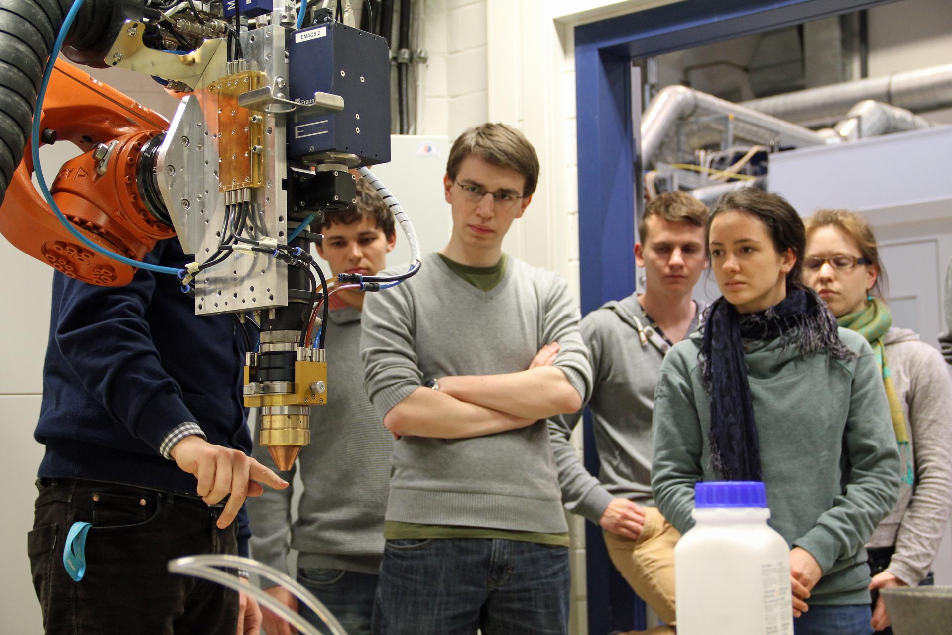 Fünf Studierende betrachten einen Industrieroboterarm, an dem ein Laserkopf befestig ist.