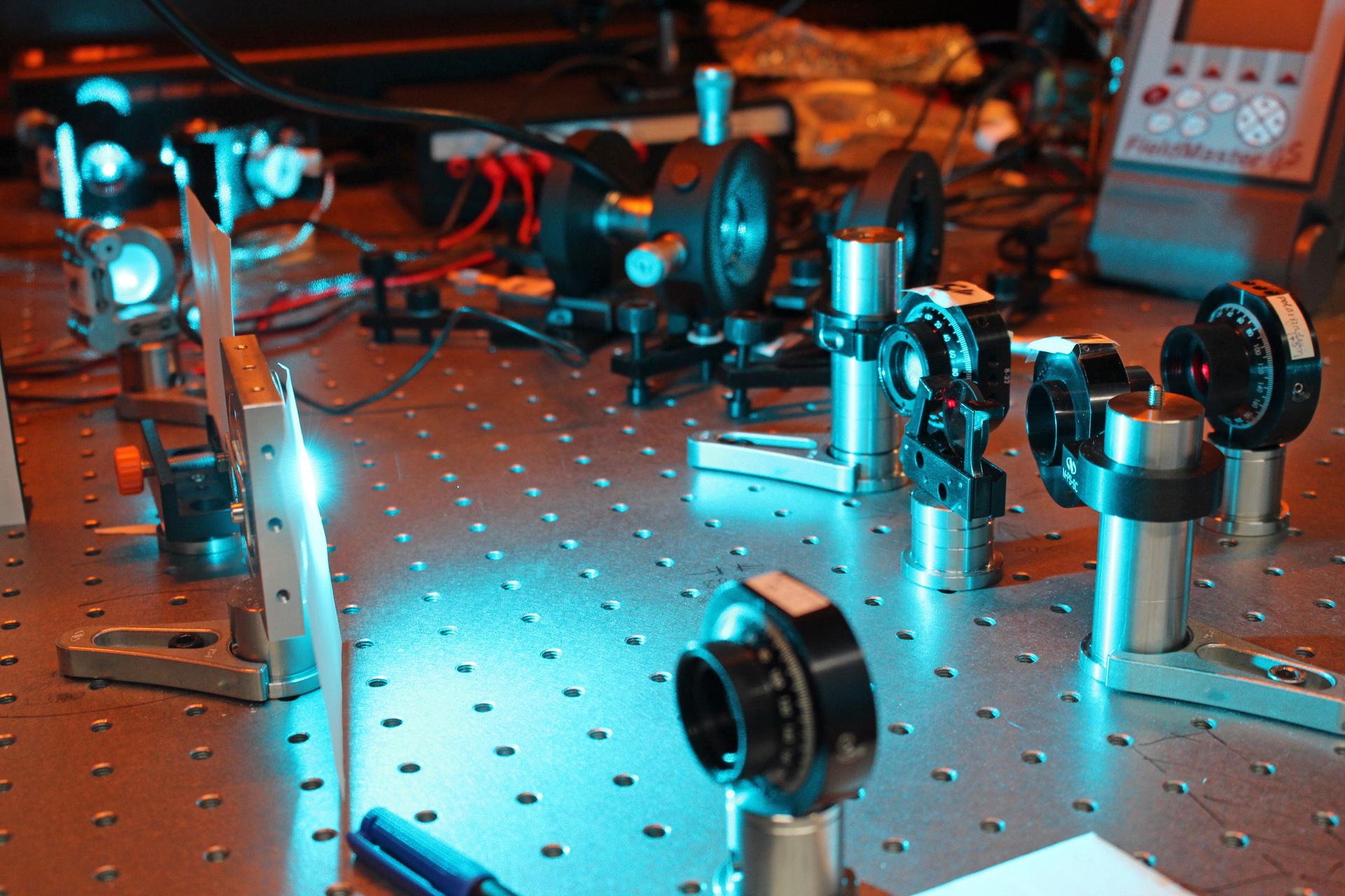 Spezieller Laser-Aufbau im Labor mit einem blauen Laser und optischen Linsen.