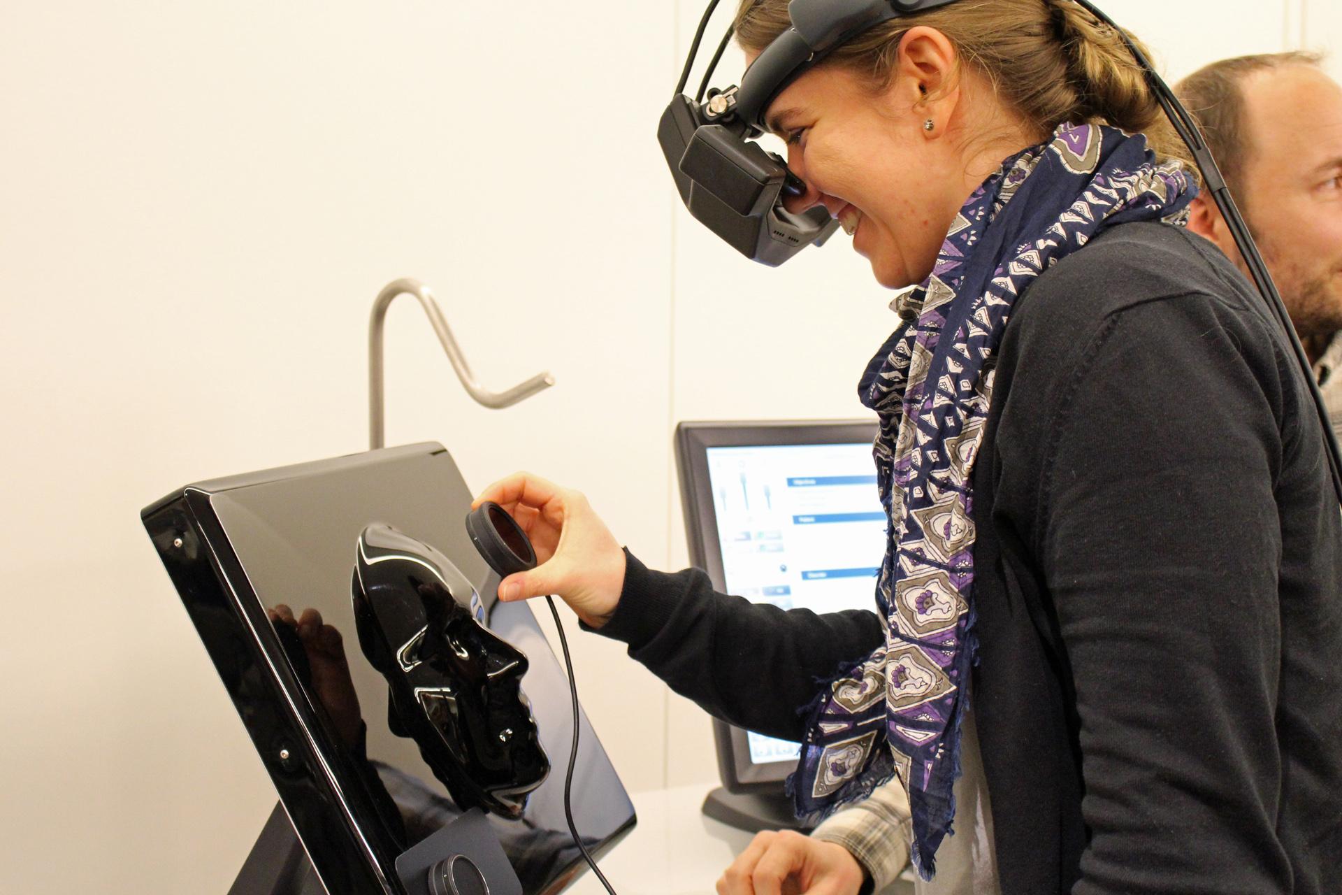 Frau hat eine Hightech-Brille an und einem kleinen Sensor in der Hand, den sie über einem Plastikkopf hält.