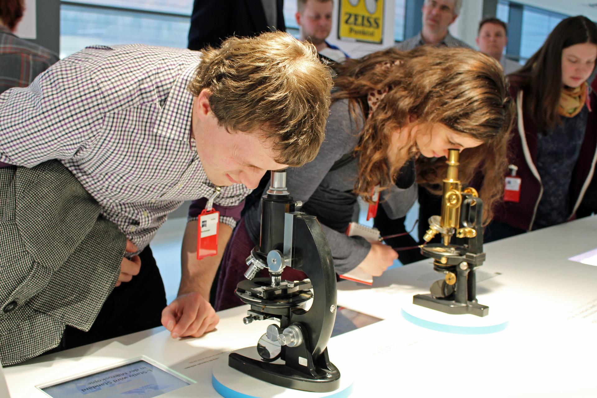 Ein Mann und eine Frau blicken durch zwei altmodische optische Mikroskope.