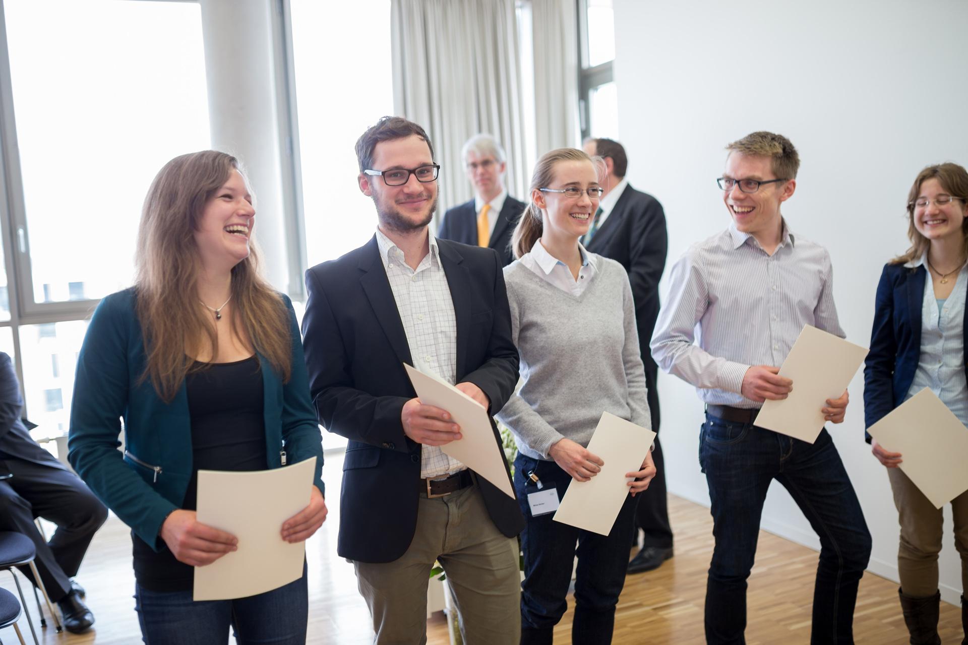 Fünf fröhliche Studierende mit Urkunde.