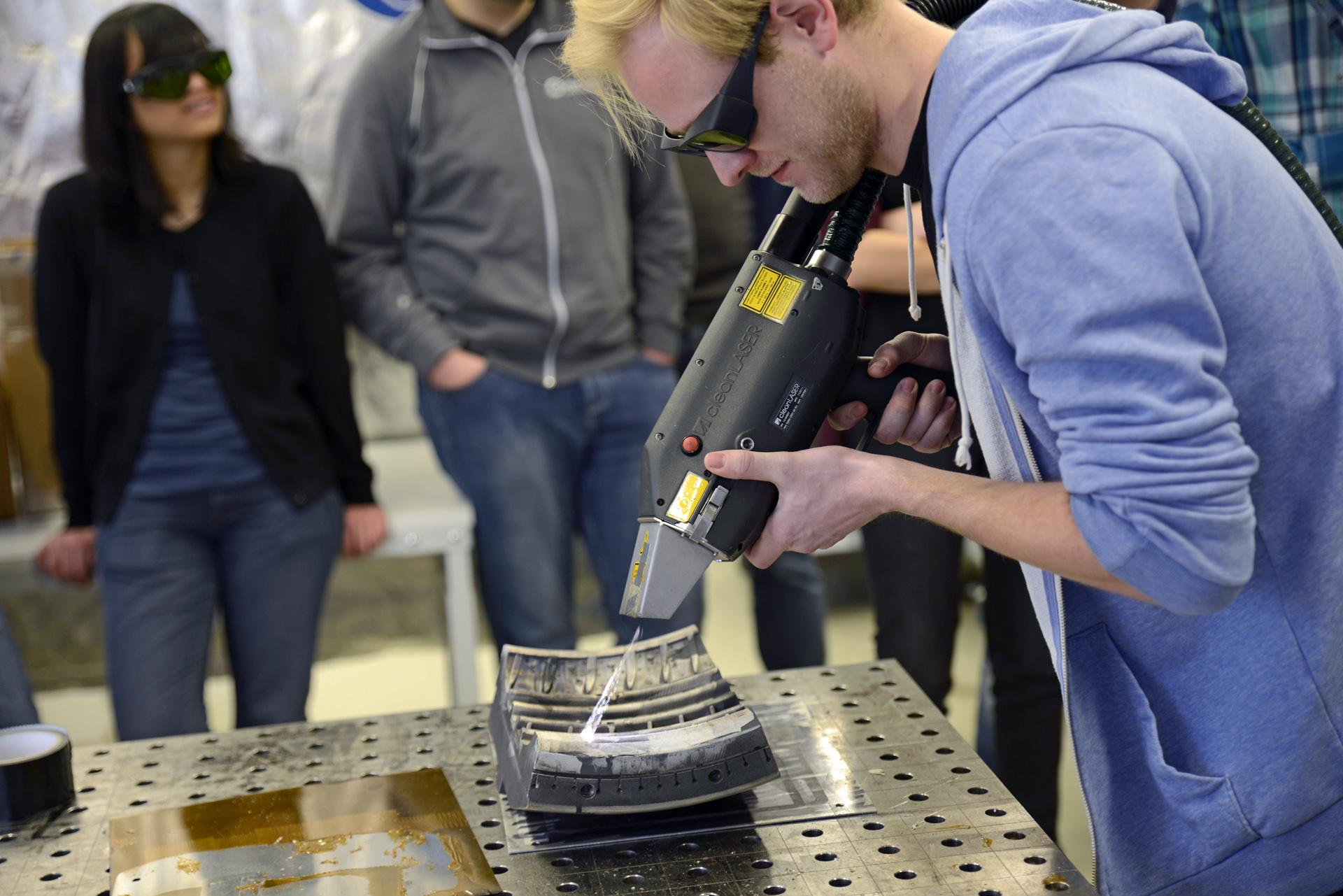 Mann reinigt mit einem Laser eine Metalloberfläche
